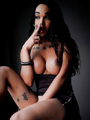 Busty tranny Adriana smoking at the window
